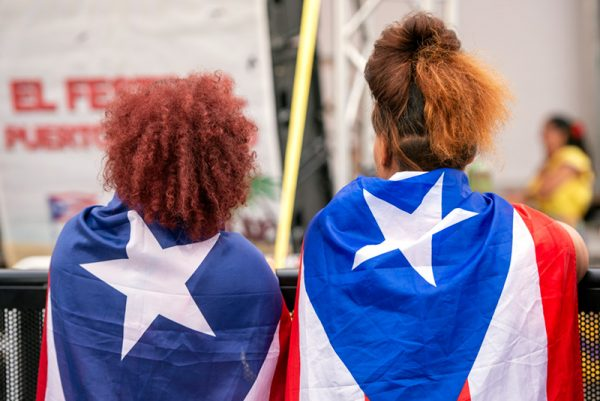 Festivalgoers wear Puerto Rican flags as capes Aug. 16.