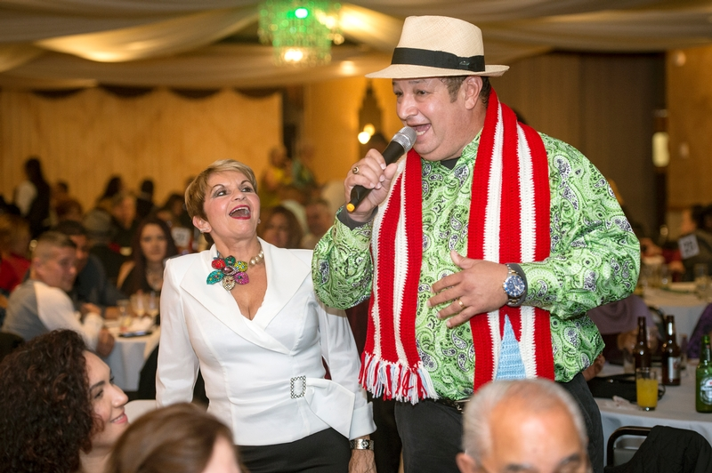 Ibero-American Action League President and CEO Hilda Rosario Escher (left) laughs during a song performed by Jovino González during the fourth-annual Aires Navideños: Parranda Jibara Puertorriqueña Dec. 1 at The Diplomat banquet center.