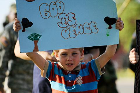 Samuel Carey, 7, carries a sign.