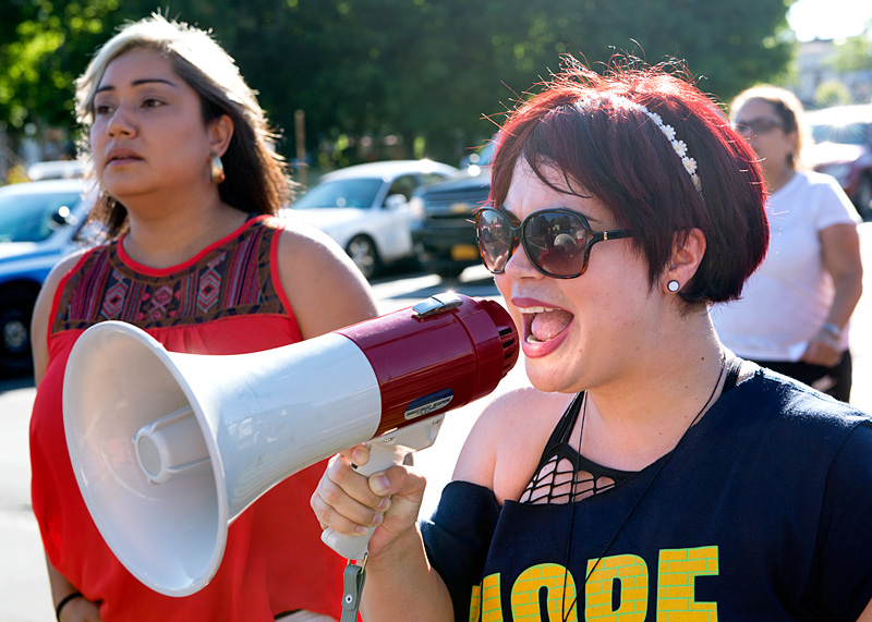 Sacha Rios of Project HOPE uses a megaphone to lead a peace chant.