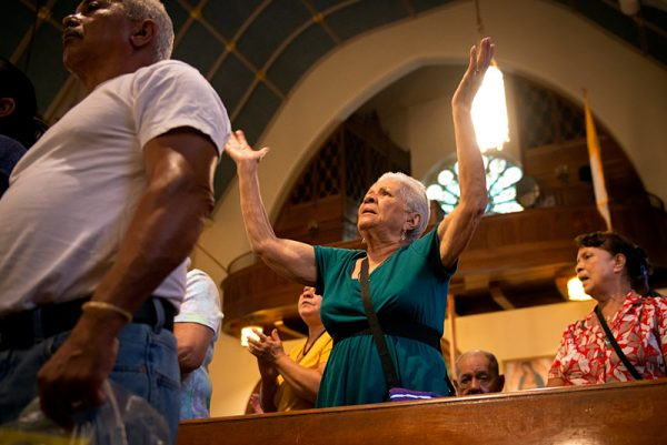 Monserrade Santiago raises her hands in a prayer during a Mass on the second day of the mission.