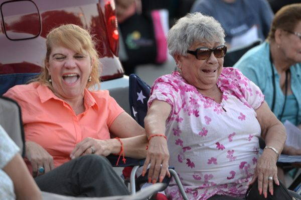 Elisabet Reyes, left, and Carmen Barbosa share a laugh during a comedy skit put on by children during the annual Santa Misión 2016 for the Latino community at St. Michael Church in Rochester, Monday Aug. 8.