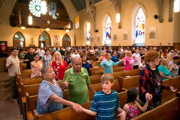 Mission participants hold hands during Mass on the second day of the mission.
