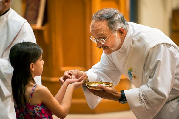 Deacon Carlos Vargas distributes the Eucharist during Mass on the second day of the mission.
