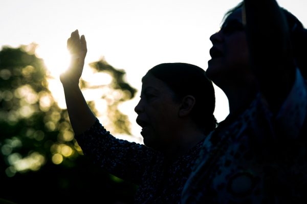 Mission participants raise their hands in worship on the third day.