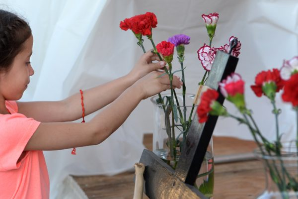 Mariana Albino, 7, places a carnation during the live rosary recital during the annual Santa Misión 2016 for the Latino community at St. Michael Church in Rochester, Monday Aug. 8.