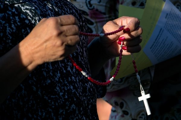 A mission participant prays the rosary on the third day of the event.