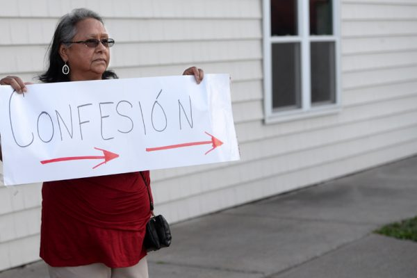 Arles Medero holds a sign for confession during the annual Santa Misión 2016 for the Latino community at St. Michael Church in Rochester, Monday Aug. 8.