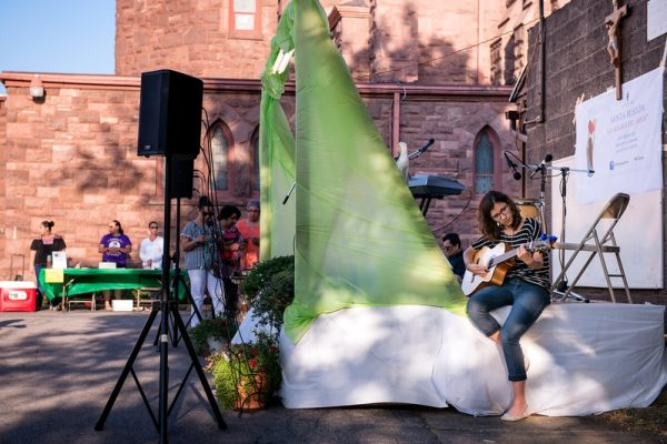 Emily Cuellar tunes a guitar before the start of the celebration on the mission's third day.