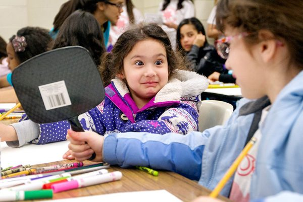 Six-year-old Alejandra Ochoa gets help from her sister, 8-year-old Adriana Ochoa, to use a mirror while creating a self portrait during a student workshop at ¡Soy Unica! ¡Soy Latina! Rally April 19 at Nazareth College.