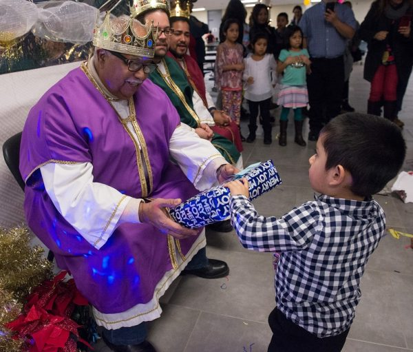 Three-year-old Daniel Lagunas receives a gift from one of the Three Kings during a Christmas Fiesta at Brockport High School Jan 20.