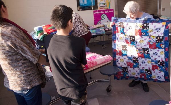 Barb Deming holds one of the more than 70 quilts that families could choose from during a Christmas Fiesta at Brockport High School Jan 20.