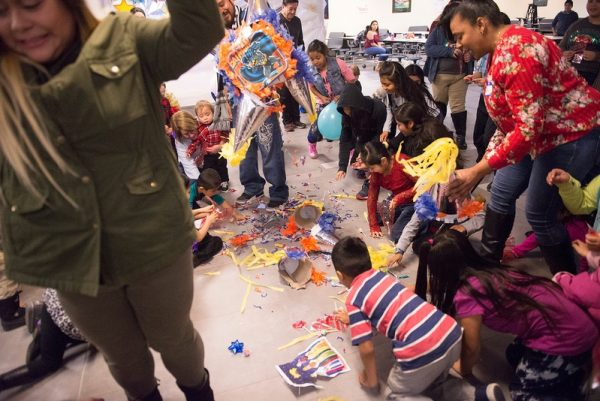 Children dive for candy that fell from a broken pinata during a Christmas Fiesta at Brockport High School Jan 20.
