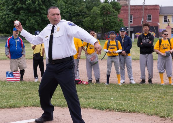 Fabian Rivera of the Rochester Police Department throws out the first pitch to open the Rochester Hispanic Youth Baseball League's 2018 season June 2.