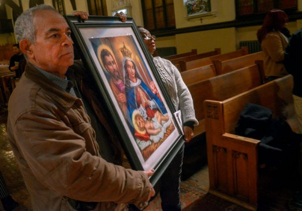 Frank and Diogenia Batista carry an image of Our Lady of Altagracia during a Jan. 21 Mass at Rochester's Our Lady of the Americas Church.