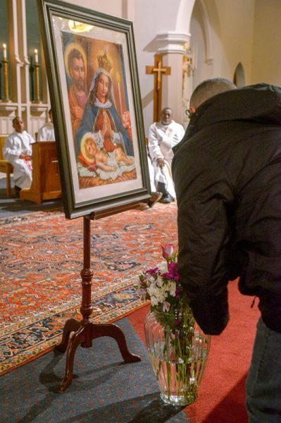 Flowers are placed before the image of Our Lady of Altagracia.