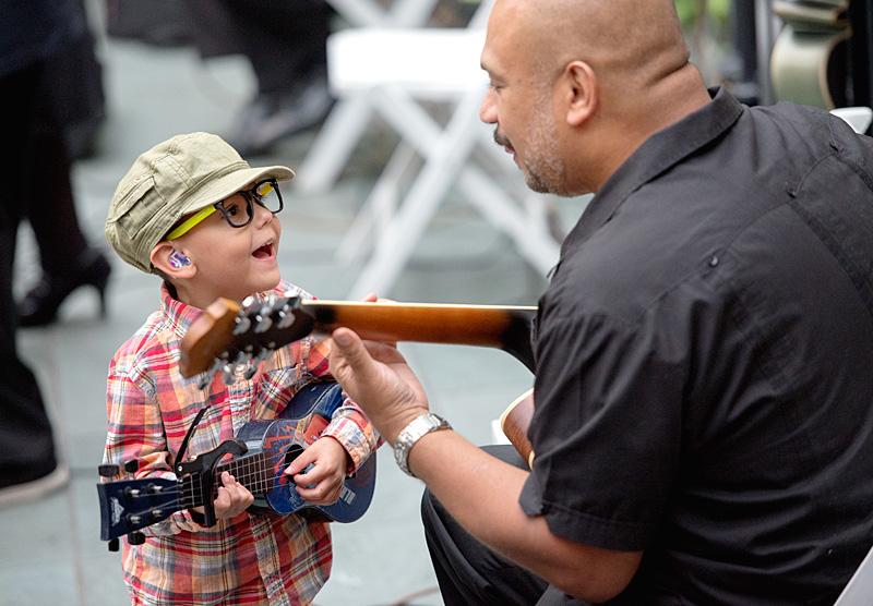 Four-year-old Julian Muñoz trades guitar licks with Conjunto Típico guitarist Orlando Nuñez.