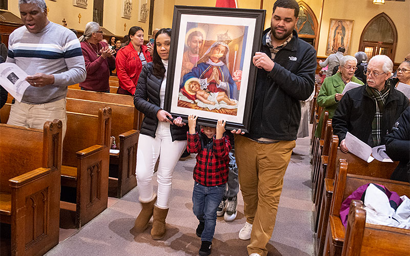Family carries image of Our Lady of Altagracia.