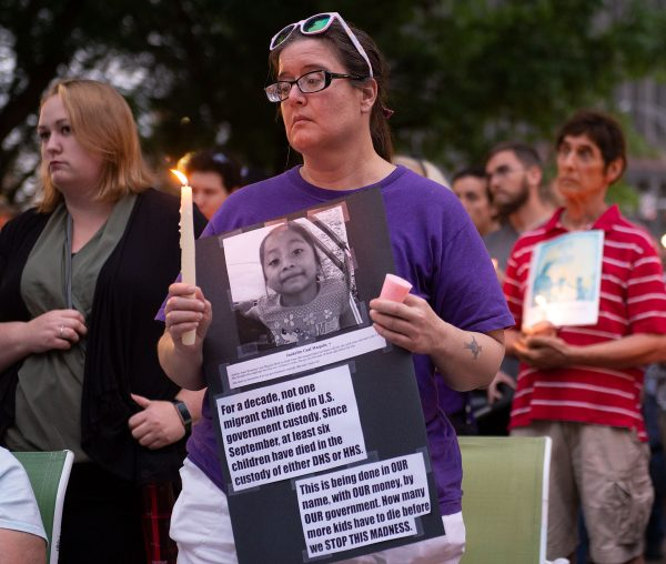 A woman holds a sign and candle.