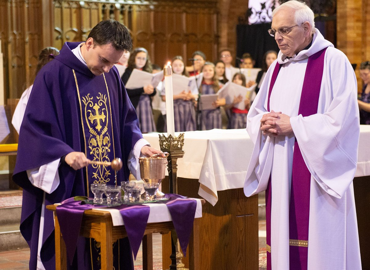 Father  Carlos Sanchez  blesses the ashes as Father Thomas Mull looks on during Ash Wednesday Mass on Feb. 26 at St. Stephen Church in Geneva. (Courier photo by John Haeger)