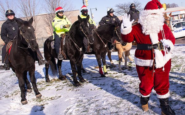 Santa waves with horses in background.