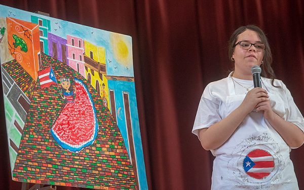 Jadisha Irizarry gives a presentation on her painting during the pageant.