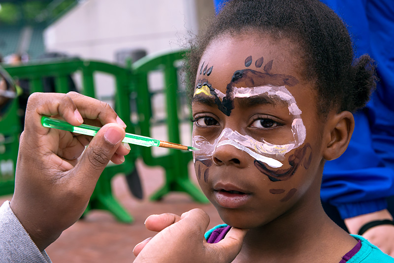 Six-year-old Malia Smith has her face painted during the Summer Meals Fest at Rochester's Frontier Field May 14.